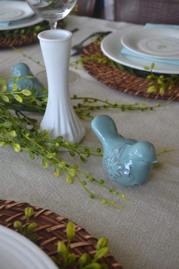 Greenery and blue Easter tablescape with bird centerpiece and whicker placemats.