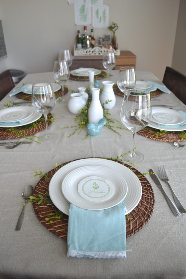 Greenery and blue Easter tablescape with bird centerpiece and whicker placemats